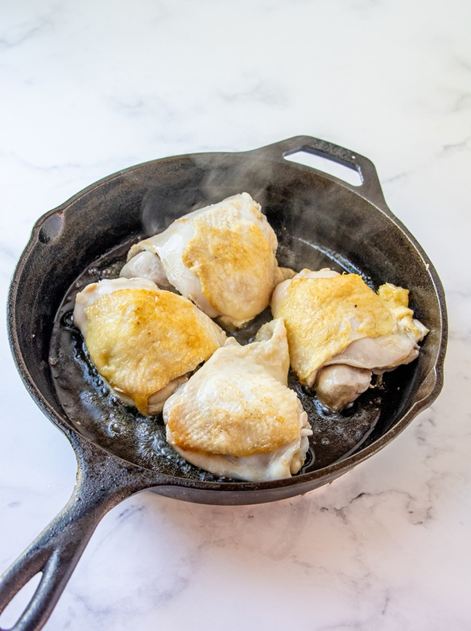 searing chicken thighs in a cast iron skillet