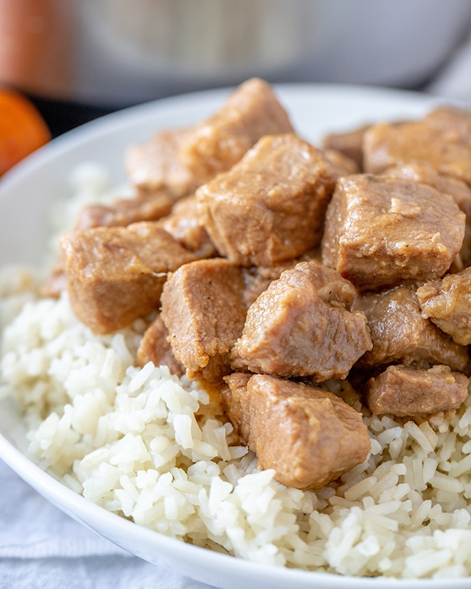 Pressure cooker pork adobo on steamed rice on a white plate