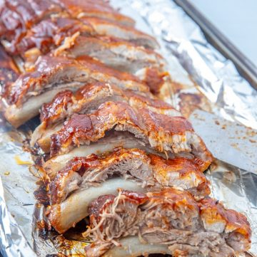 cut slab of Instant Pot BBQ pork ribs on a foil-lined baking sheet