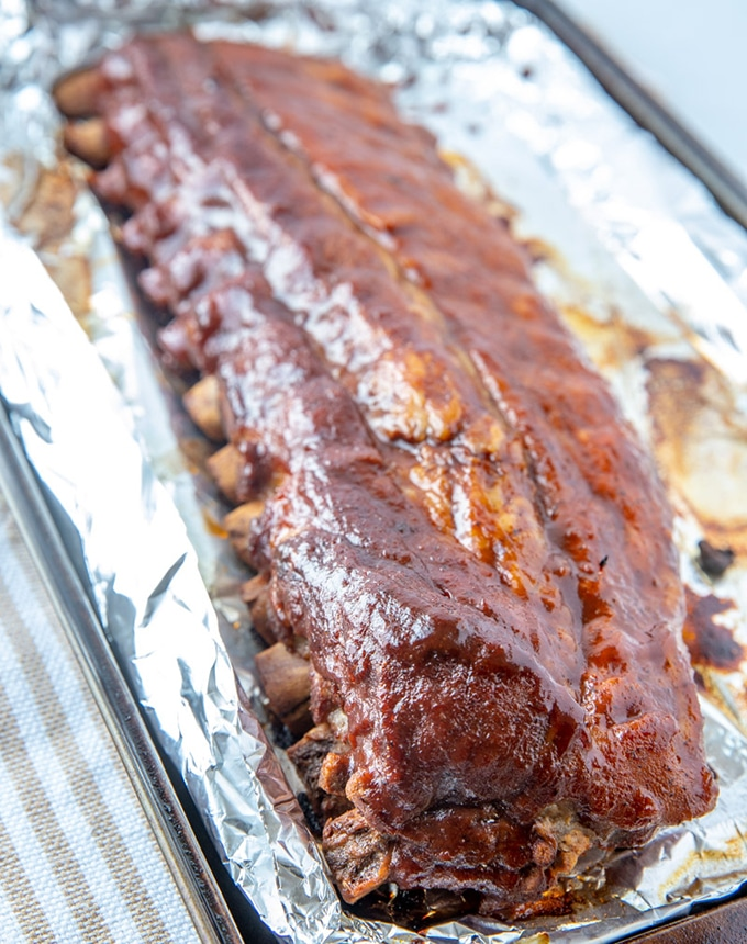 Instant Pot Ribs With Coca-Cola BBQ Sauce on a foil-lined baking sheet