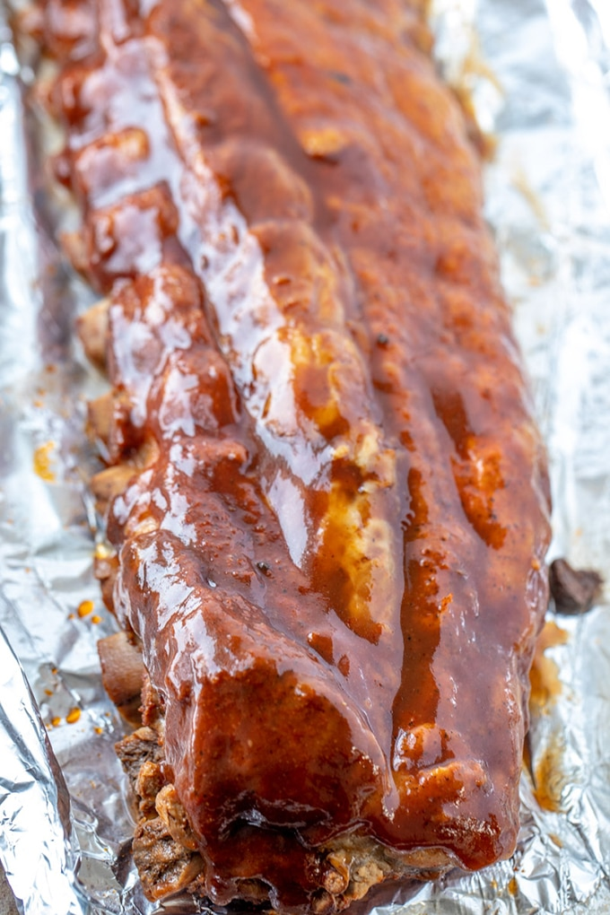 pressure-cooked ribs on a baking basted with cola BBQ sauce