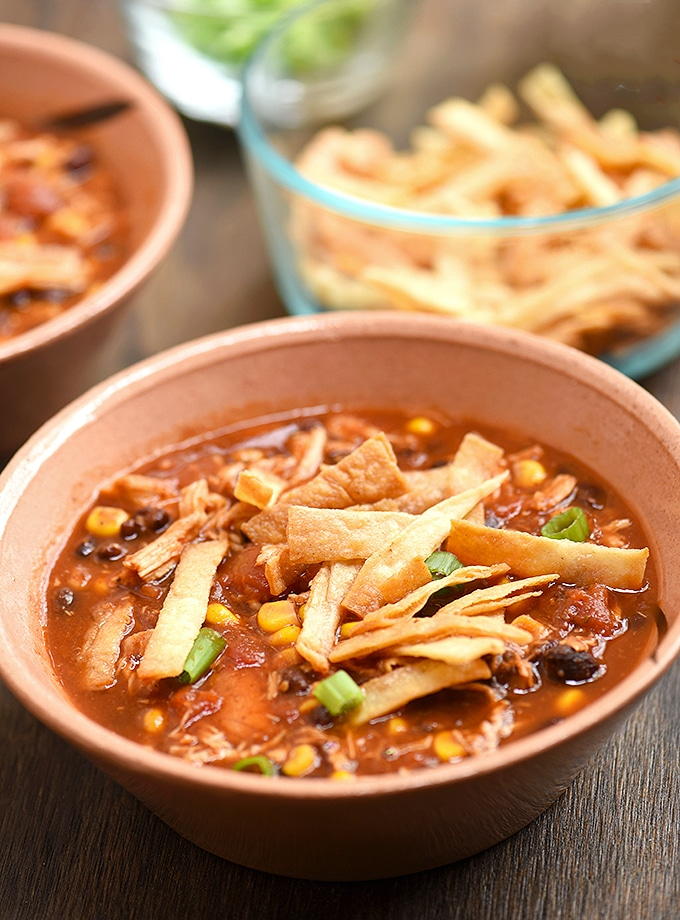 Slow Cooker Chicken Tortilla Soup in a bowl with a side bowl of fried tortilla chips