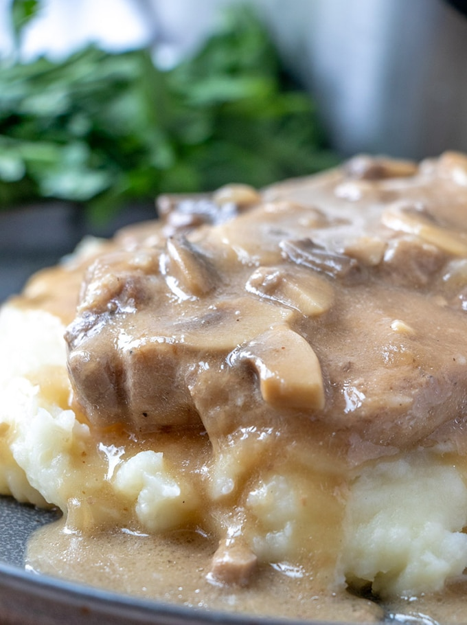 smothered pork chops cooked in Instant Pot over mashed potatoes