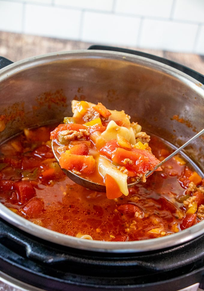 serving lasagna soup with a large soup ladle from the Instant Pot