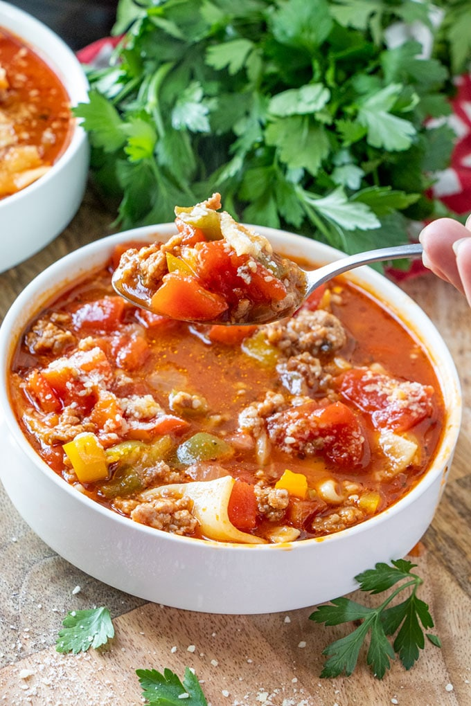eating Instant Pot Lasagna soup with a spoon form a white bowl