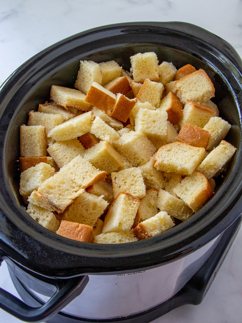 cubed brioche bread in a a slow cooker