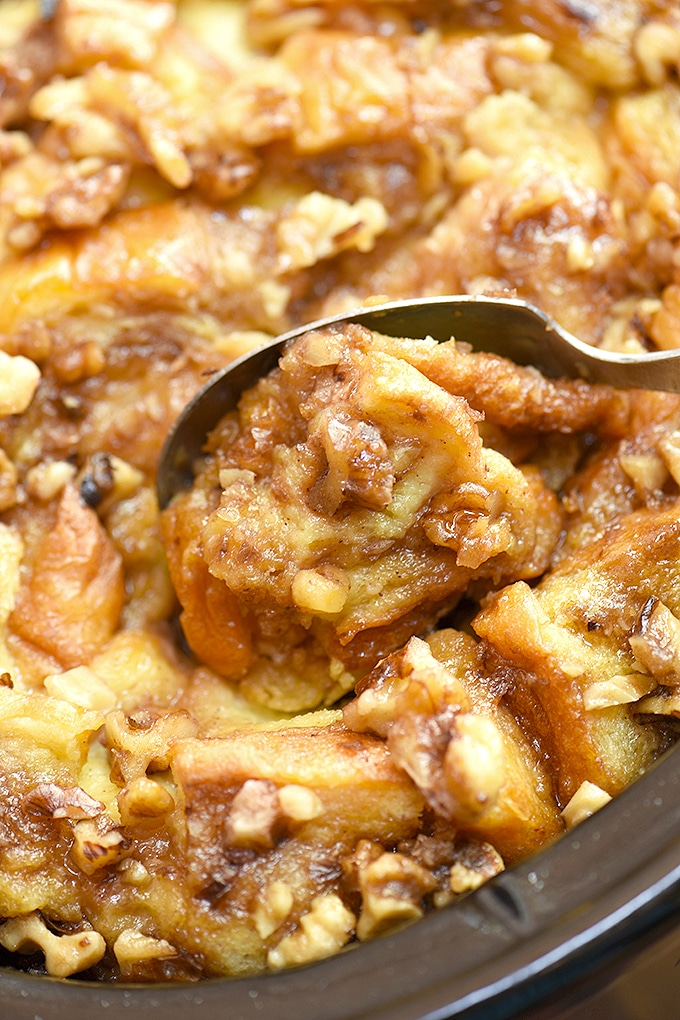 serving french toast casserole with a large spoon from the crockpot
