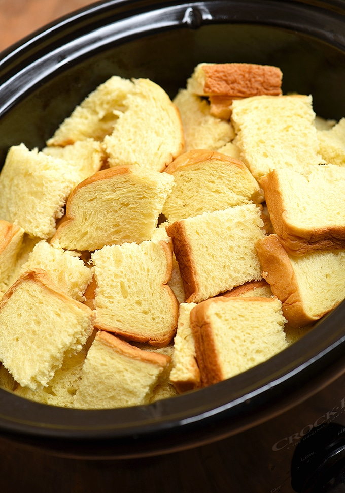 cubed brioche bread in a black slow cooker