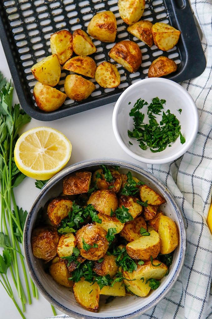 air fryer roasted potatoes with Greek seasonings in a bowl with sliced lemon and chopped parsley on the side