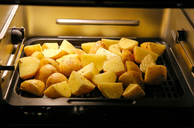 cut baby potatoes roasting in the air fryer