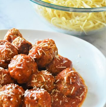 Instant Pot Turkey Meatballs with marinara sauce on a white plate with shredded Parmesan cheese on the side