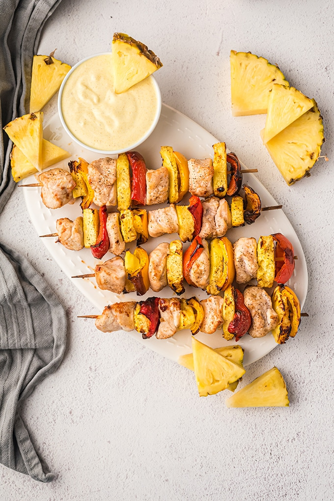 Hawaiian chicken kabobs with pineapples and bell peppers on a white platter