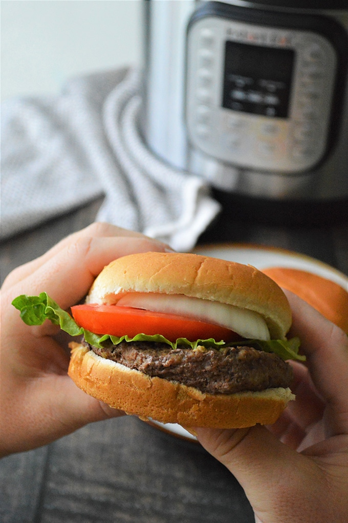 holding steamed burger with hands