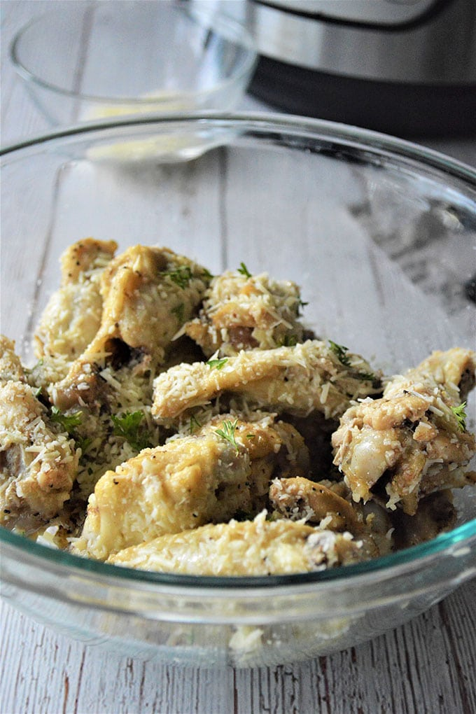 pressure cooker chicken wings with garlic butter parmesan in a clear bowl