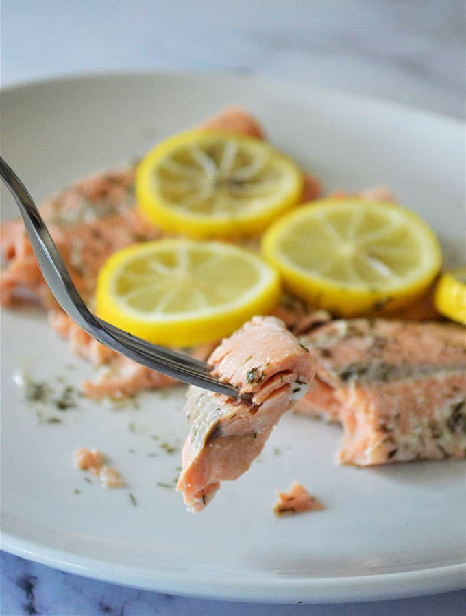 eating lemon dill salmon with a fork from a white plate