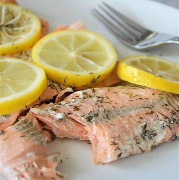 pressure cooker lemon dill salmon with sliced lemons on a white plate