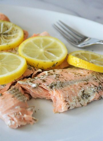 pressure cooker lemon dill salmon with sliced lemons on a white plate