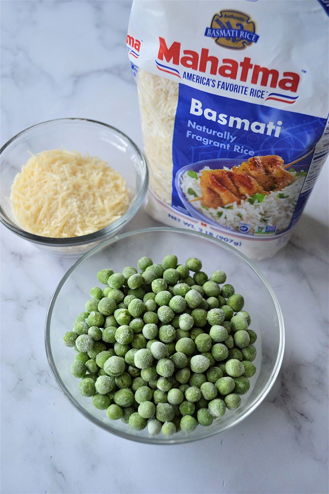 Basmati rice in package and bowls of Parmesan cheese and frozen green peas on the side