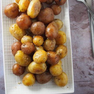 Instant Pot Baby Potatoes with Garlic Herb Butter on a white platter