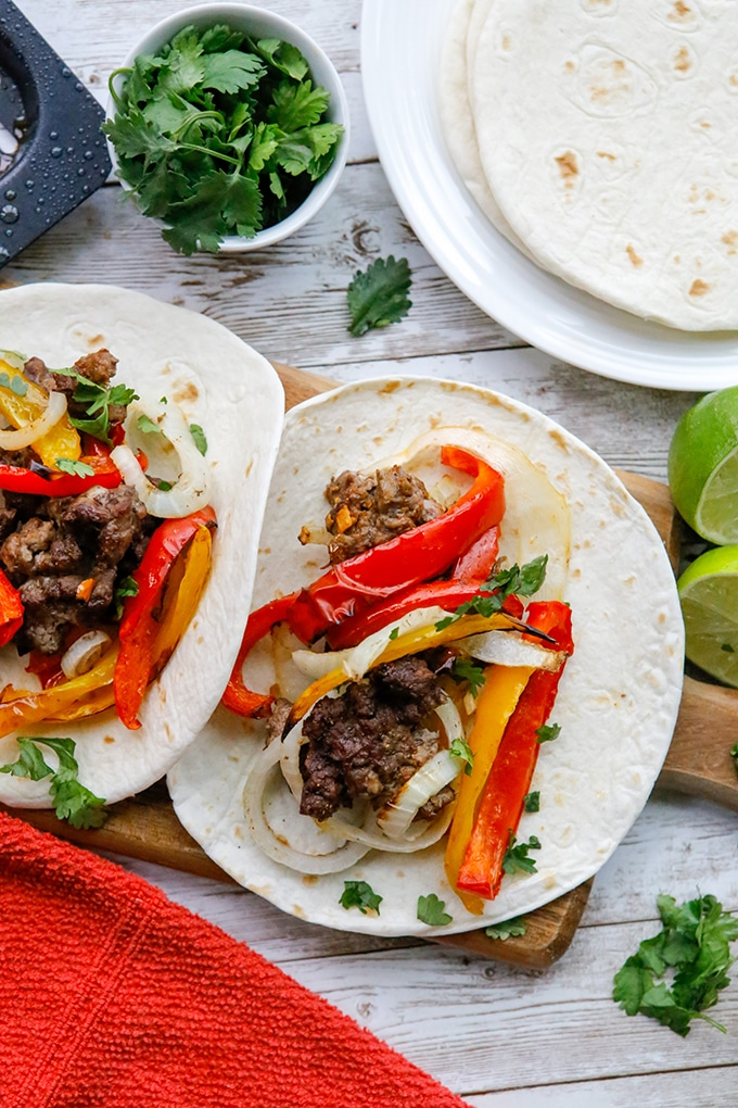 steak fajitas with onions and bell peppers on flour tortillas