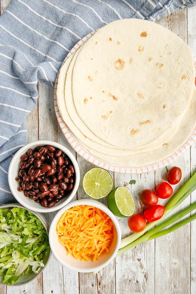 floiur tortillas, refried beans, shredded lettuce, cherry tomatoes, green onions, limes