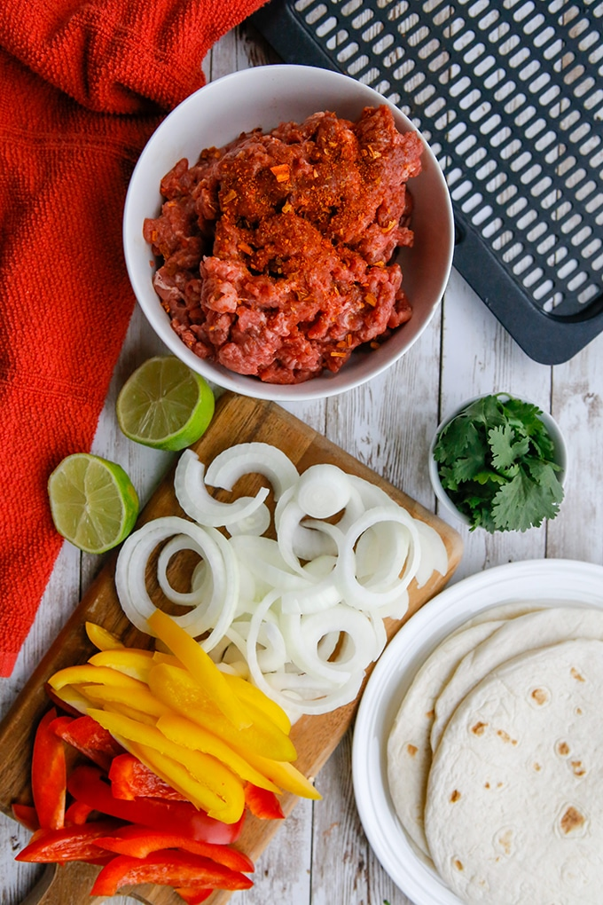 raw flank steak strips, sliced onions, bell peppers, and flour tortillas