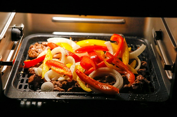 beef fajitas with onions and bell peppers cooking in an air fryer