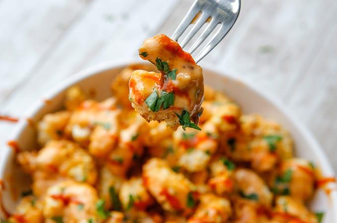 serving crispy shrimp with bang bang sauce in a fork