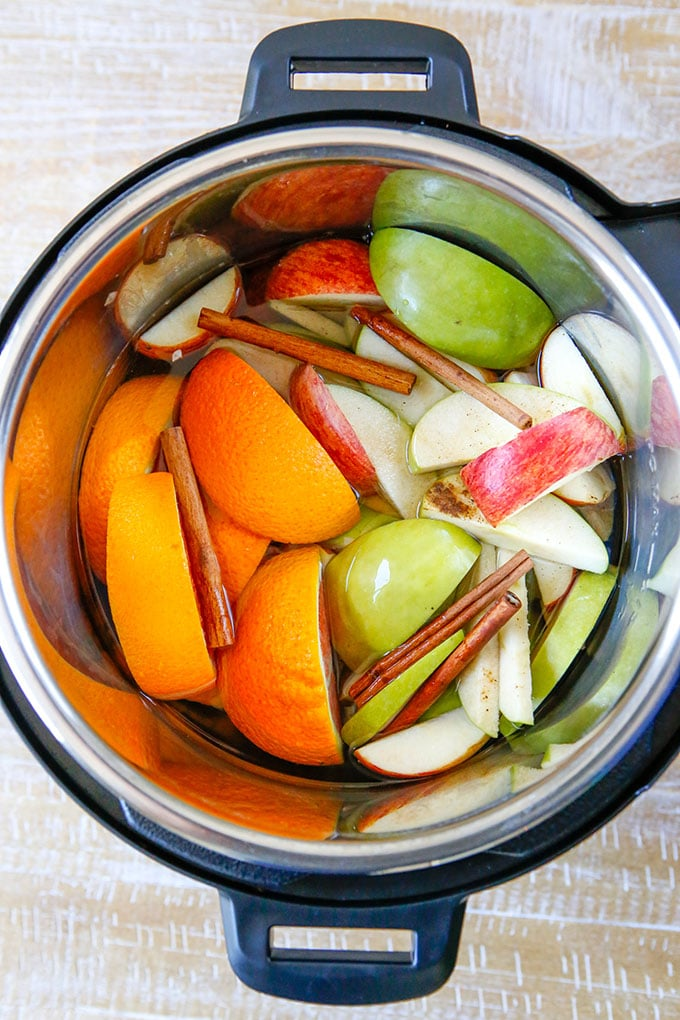 sliced apples, sliced oranges, cinnamon sticks in the Instant Pot