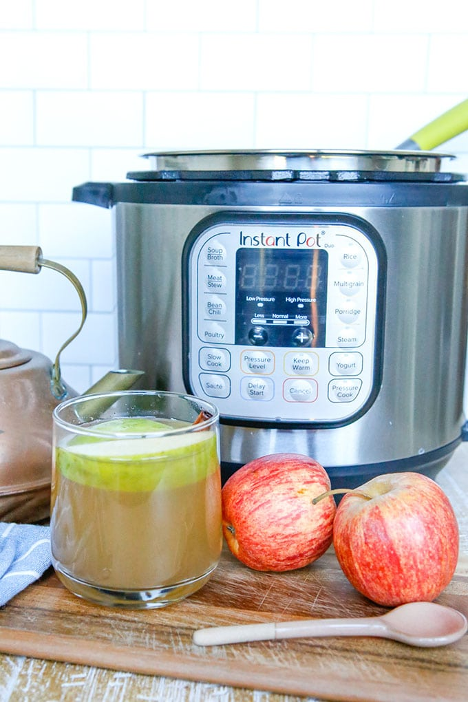 Instant Pot Apple Cider in a clear mug with apples and an Instant Pot on the side