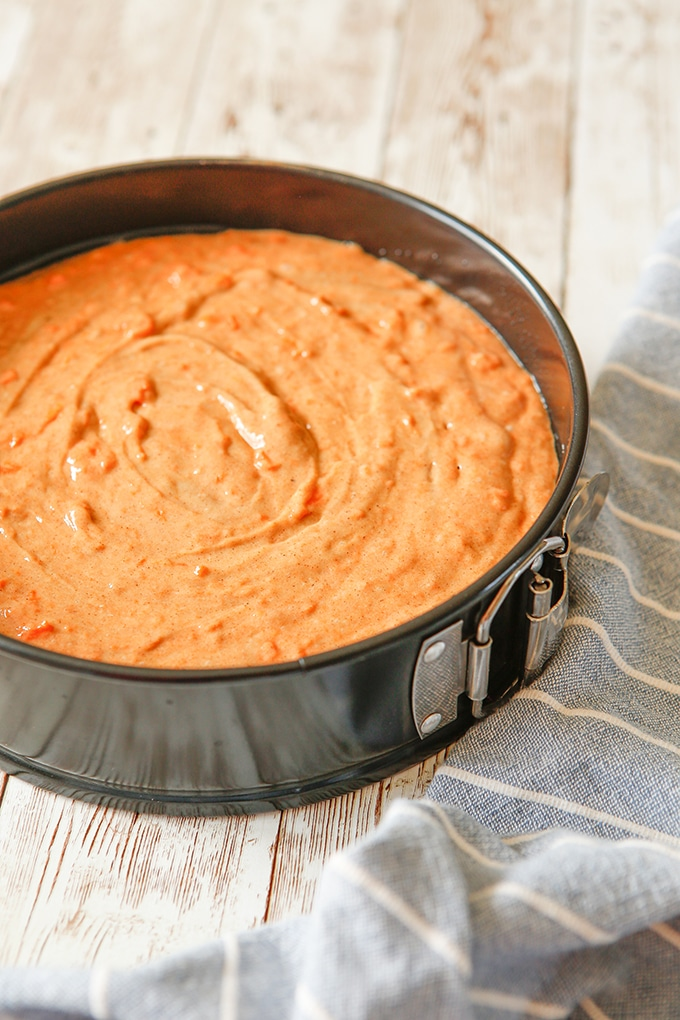 spice cake batter with grated carrots in a springform pan