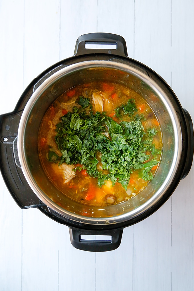 cooked chicken and rice soup with kale in the pressure cooker