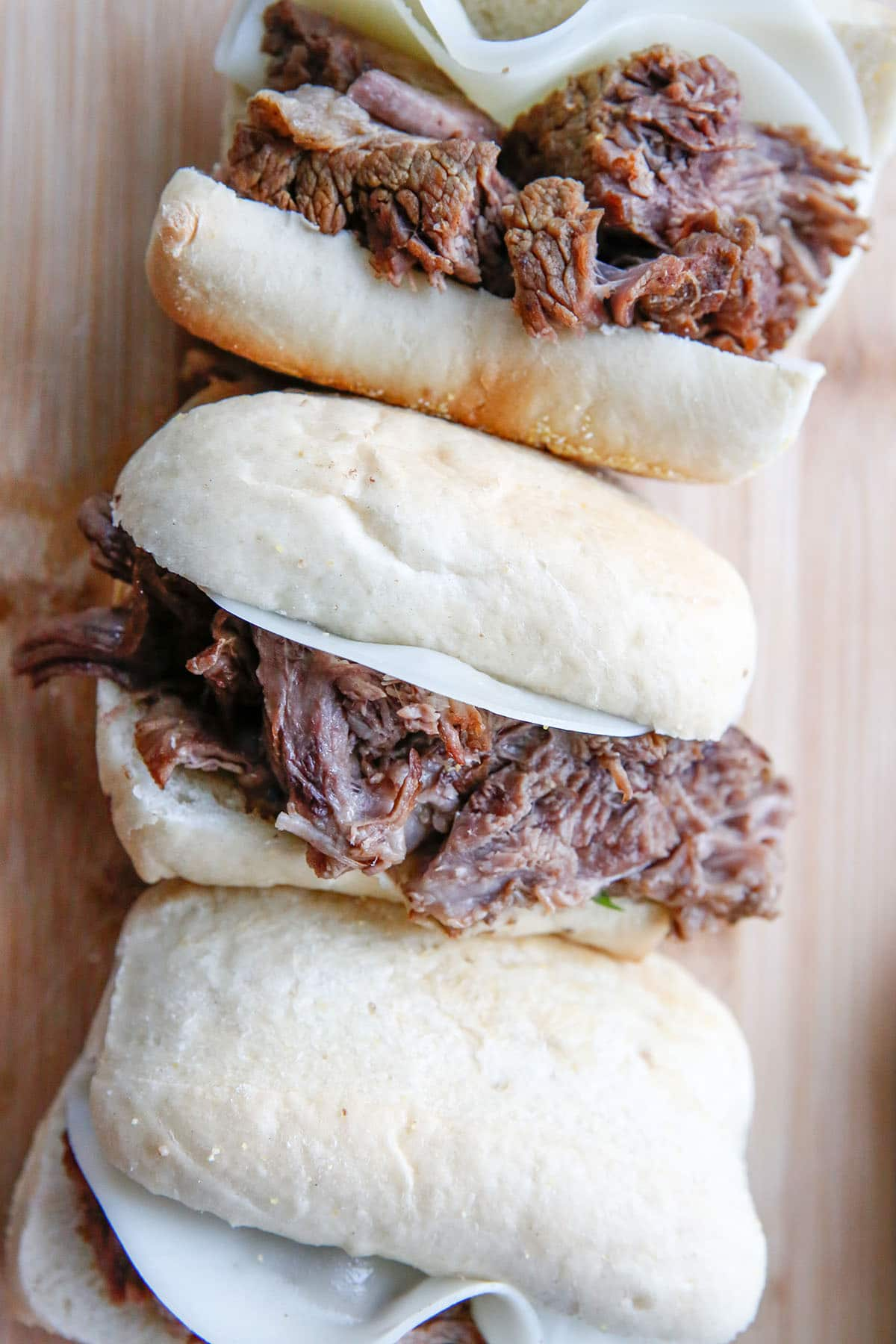 beef dip sandwiches on a wooden board