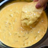 dipping corn chips in slow cooker queso dip
