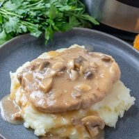 Instant Pot Pork Chops with Mushroom Gravy on a serving plate over mashed potatoes